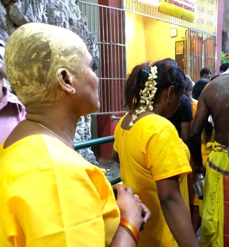 Součástí tradice je i oholení hlavy a pomazání žlutou barvou. Na obrázku jedna z mnoha žen, která se svých vlasů zbavila.